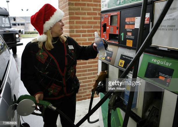 Valerie Doster looks at her gasoline purchase while filling her tank at a gas station December 22 2006 in Dunkirk Maryland Gas prices have risen only...