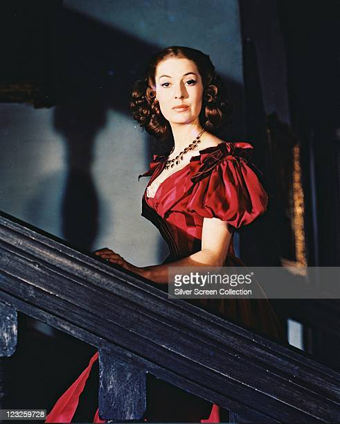 Valerie Hobson wearing a lowcut red dress with short balloon sleeves with one hand on the banister as she walks up a flight of stairs circa 1955