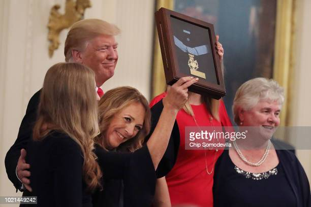 Valerie Nessel wife of Air Force Technical Sergeant John Chapman holds up her husband's Medal of Honor during a ceremony at the White House with her...