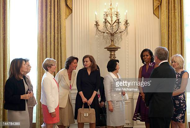 Valerie Trierweiler listens to an interpreter as US first lady Michelle Obama hosts the spouses of G8 leaders at the White House for a tour May 19...