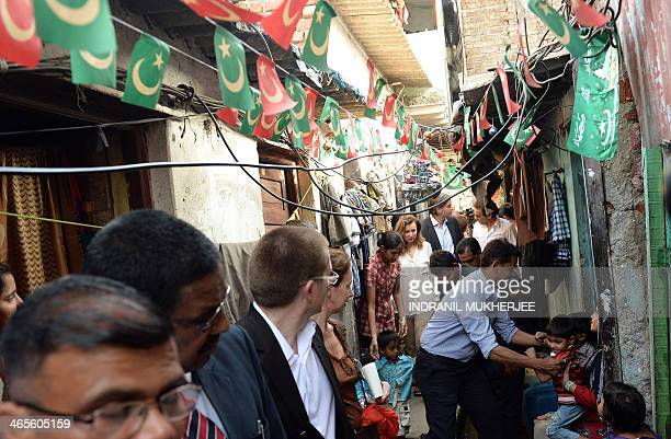 Valerie Trierweiler the expartner of French President Francois Hollande walks through a narrow alley during a visit to the Ekta Nagar slums in the...