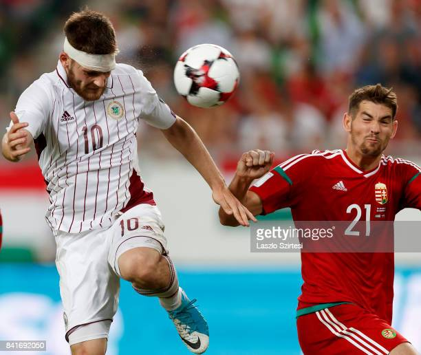 Valerijs Sabala of Latvia heads the ball next to Barnabas Bese of Hungary during the FIFA 2018 World Cup Qualifier match between Hungary and Latvia...