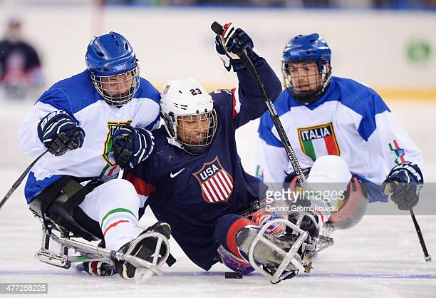 Valerio Corvino of Italy challenges Rico Roman of the United States during the Ice Sledge Hockey Preliminary Round Group A match between the United...