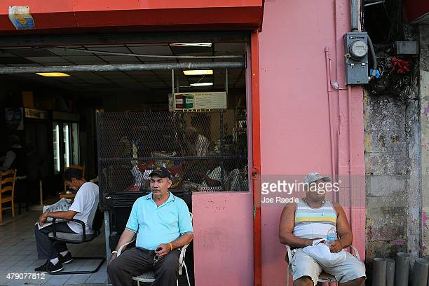 Valerio Ginairs and Ricardo de la Cruz relax outside a bar a day after Puerto Rican Governor Alejandro Garcia Padilla gave a televised speech...