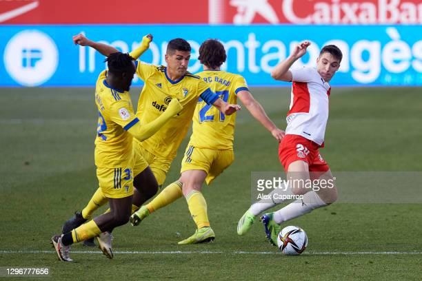 Valery Fernandez of Girona FC battles for possession with Habeeb Omobolaji 'Boddy' Adekanye, Jon Ander Garrido and Marc Baro of Cadiz CF during the...