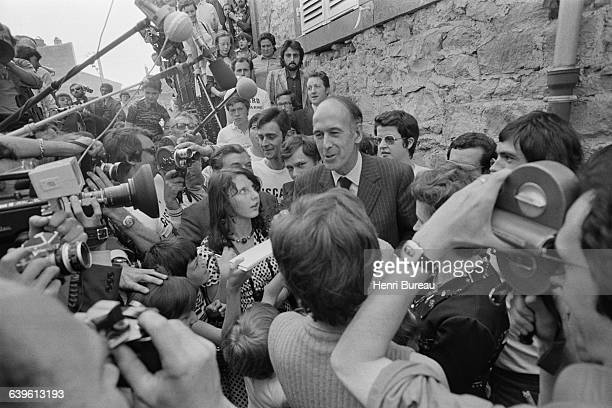 Valery Giscard d'Estaing heads to the polls to vote at Chamalières town hall of which he is deputy mayor Wellwishers some wearing tshirts marked...