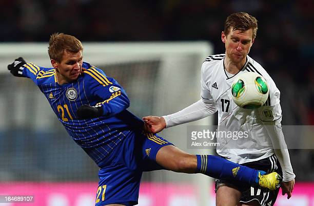Valery Korobkin of Kazakhstan is challenged by Per Mertesacker of Germany during the FIFA 2014 World Cup qualifier between Germany and Kazakhstan at...