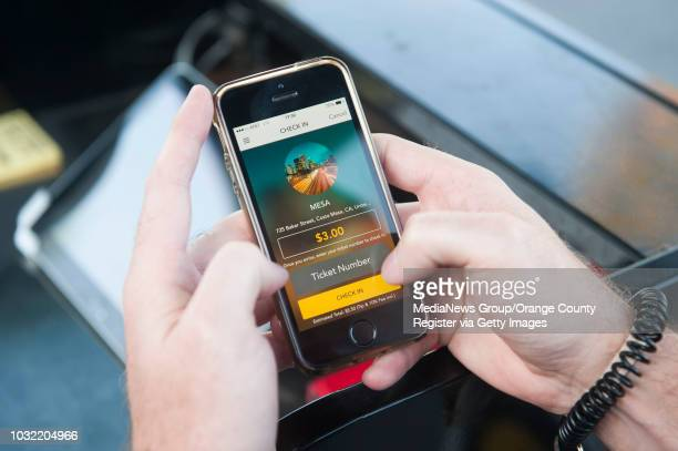 Valet Dan Salee of Irvine demonstrates the Curbstand App outside the Mesa Lounge at The Camp in Costa Mesa Tuesday INFO parking0415kjs Photo by KEVIN...
