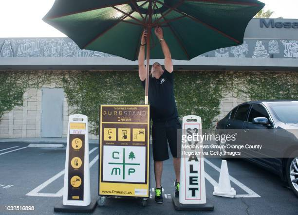 Valet Dan Salee of Irvine sets up his umbrella after opening for the night outside the Mesa Lounge at The Camp in Costa Mesa Tuesday INFO...