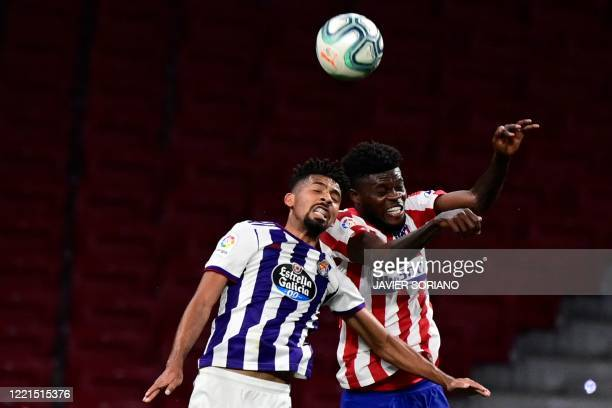 Valladolid's Brazilian midfielder Matheus Fernandes and Atletico Madrid's Ghanaian midfielder Thomas Partey jump for the ball during the Spanish...