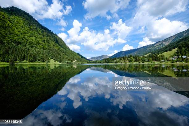 valley between hills against cloudy sky reflecting on water surface - savoie stock pictures, royalty-free photos & images