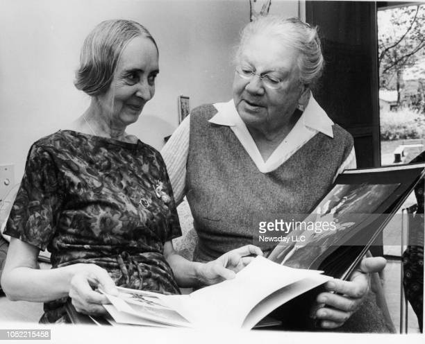 Former prima ballerina Olga Spessivtseva looks at photos with Countess Alexandra Tolstoy at Reed Farm in Valley Cottage New York on May 4 1964...