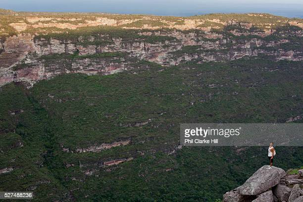 Valley de Capao famaca waterfall valley with young man standing on a rock looking at the view at dusk Chapada Diamantina national park in Bahia...