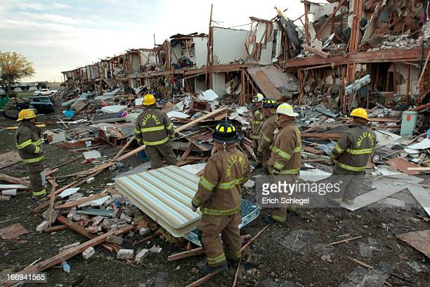 Valley Mills Fire Department personnel walk among the remains of an apartment complex next to the fertilizer plant that exploded yesterday afternoon...