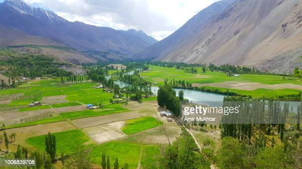 valley surrounded with mountains and lake - gilgit baltistan stock photos and pictures