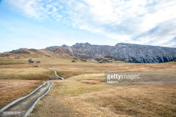 valley with little wooden cottages and mountain range in the background. autumn in the dolomites. seiser alm. - alto adige bildbanksfoton och bilder