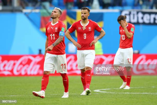 Valon Behrami Haris Seferovic and Ricardo Rodriguez of Switzerland walk off the pitch dejected following the 2018 FIFA World Cup Russia Round of 16...