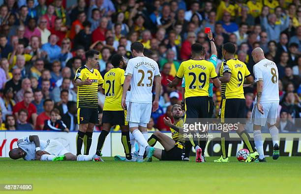 Valon Behrami of Watford is shown the red card by referee Robert Madley during the Barclays Premier League match between Watford and Swansea City at...