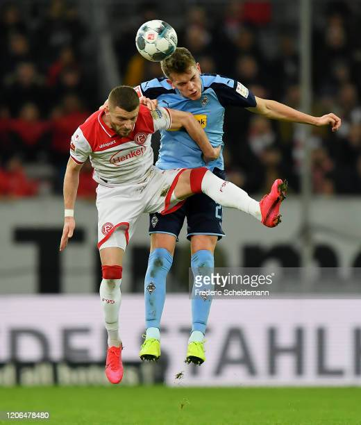 Valon Berisha of Duesseldorf jumps for a header with Matthias Ginter of Borussia Moenchengladbach during the Bundesliga match between Fortuna...