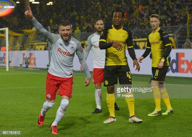 Valon Berisha of Salzburg gestures and Michy Batshuayi of Dortmund and Marco Reus of Dortmund look on during UEFA Europa League Round of 16 match...