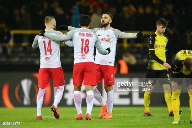 Valon Berisha Takumi Minamino and Munas Dabbur of Red Bull Salzburg celebrate victory after the UEFA Europa League Round of 16 match between Borussia...