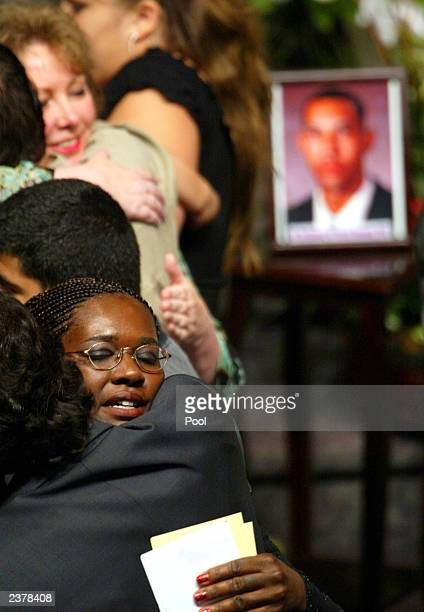 Valorie Brabazon gets hugs from family and friends near photos of her son Patrick James Dennehy following memorial services for Dennehy August 7 2003...