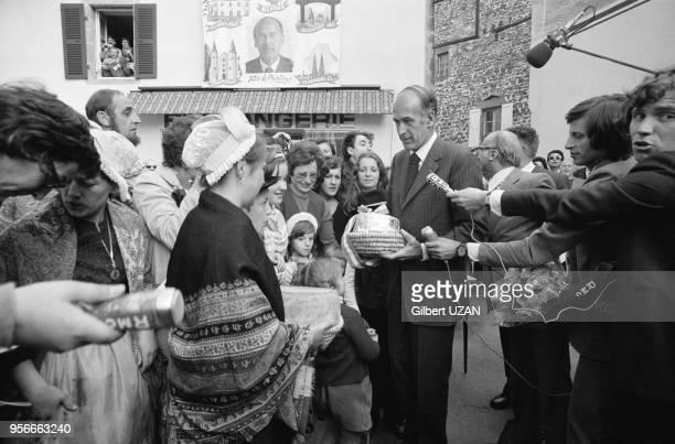 Valéry Giscard d'Estaing reçoit un cadeau des mains d'une habitante de RochefortMontagne le 8 juin 1974 France