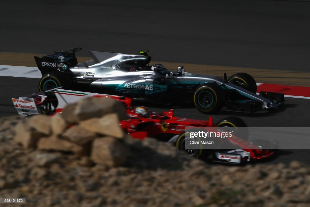 Valtteri Bottas driving the (77) Mercedes AMG Petronas F1 Team Mercedes F1 WO8 passes Sebastian Vettel of Germany driving the (5) Scuderia Ferrari SF70H on track during practice for the Bahrain Formula One Grand Prix at Bahrain International Circuit on April 14, 2017 in Bahrain, Bahrain.