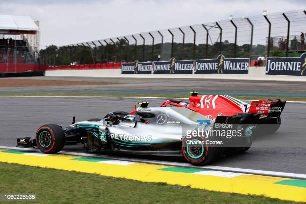 Valtteri Bottas driving the Mercedes AMG Petronas F1 Team Mercedes WO9 and Kimi Raikkonen of Finland driving the Scuderia Ferrari SF71H battle for...