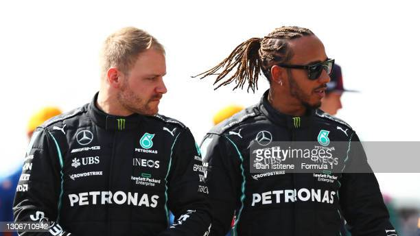 Valtteri Bottas of Finland and Mercedes GP and teammate Lewis Hamilton of Great Britain and Mercedes GP look on from the grid during Day One of F1...