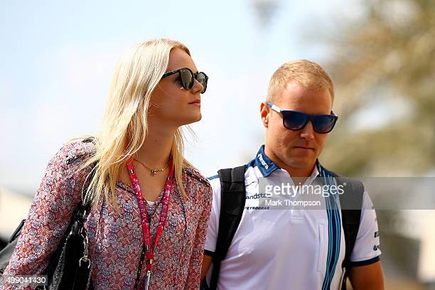 Valtteri Bottas of Finland and Williams and Emilia Pikkarainen walk in the paddock before final practice for the Abu Dhabi Formula One Grand Prix at...