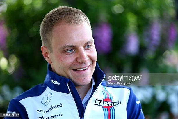 Valtteri Bottas of Finland and Williams smiles as he speaks with members of the media in the paddock during previews to the Australian Formula One...