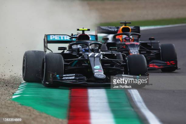 Valtteri Bottas of Finland driving the Mercedes AMG Petronas F1 Team Mercedes W11 runs wide as he leads Max Verstappen of the Netherlands driving the...