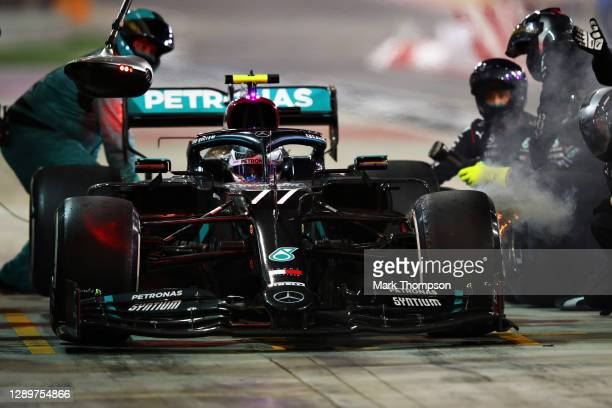 Valtteri Bottas of Finland driving the Mercedes AMG Petronas F1 Team Mercedes W11 makes a pitstop as smoke pour from his front left brake during the...