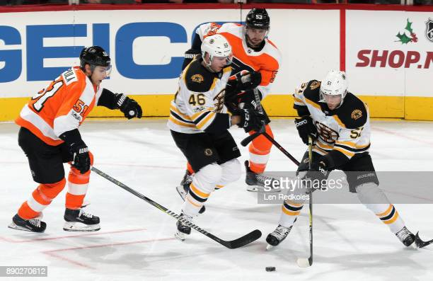 Valtteri Filppula and Shayne Gostisbehere of the Philadelphia Flyers battle for the puck against Ryan Spooner and David Krejci of the Boston Bruins...