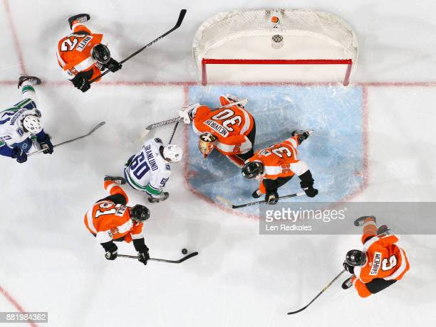Valtteri Filppula Michael Raffl Michal Neuvirth Mark Alt and Travis Sanheim of the Philadelphia Flyers scramble to clear the puck out of the crease...