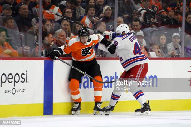 Valtteri Filppula of the Philadelphia Flyers and Rob O'Gara of the New York Rangers go after the puck in the first period at Wells Fargo Center on...