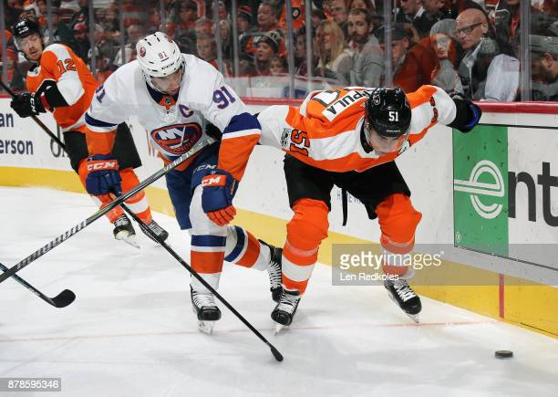 Valtteri Filppula of the Philadelphia Flyers battles for the loose puck with John Tavares of the New York Islanders on November 24 2017 at the Wells...