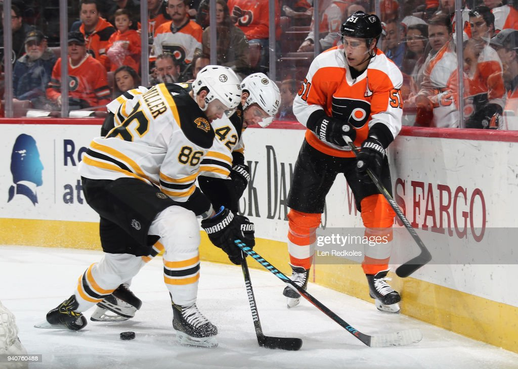 Valtteri Filppula #51 of the Philadelphia Flyers battles for the loose puck along the boards with Kevan Miller #86 and David Backes #42 of the Boston Bruins on April 1, 2018 at the Wells Fargo Center in Philadelphia, Pennsylvania. The Flyers went on to defeat the Bruins in overtime 4-3.