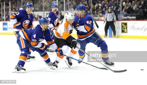 Valtteri Filppula of the Philadelphia Flyers battles for the puck against members of the New York Islanders in the third period during their game at...