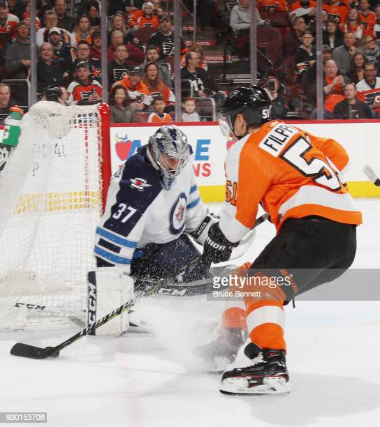 Valtteri Filppula of the Philadelphia Flyers carries the puck around Connor Hellebuyck of the Winnipeg Jets during the second period at the Wells...