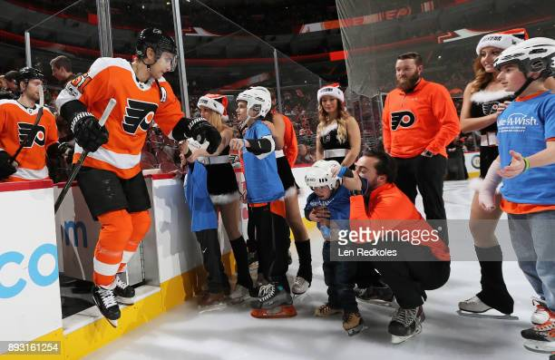 Valtteri Filppula of the Philadelphia Flyers gives members of the Philadelphia area MakeAWish Foundation high fives during pregame introductions...