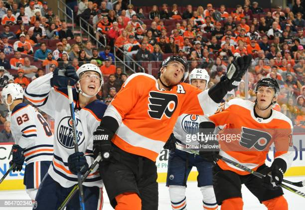 Valtteri Filppula of the Philadelphia Flyers reaches for the puck while Ryan NugentHopkins of the Edmonton Oilers defends and Jori Lehtera looks on...