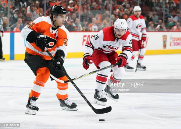 Valtteri Filppula of the Philadelphia Flyers skates the puck against Elias Lindholm of the Carolina Hurricanes on March 1 2018 at the Wells Fargo...