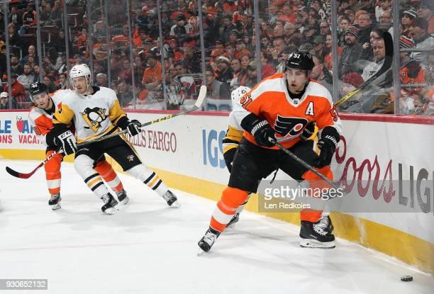 Valtteri Filppula of the Philadelphia Flyers skates the puck along the boards against the Pittsburgh Penguins with Jordan Weal defending Jamie...