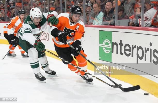 Valtteri Filppula of the Philadelphia Flyers takes the puck into the corner while being pursued by Mike Reilly of the Minnesota Wild on November 11...