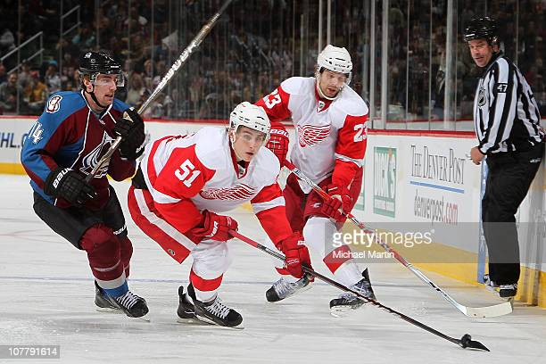 Valtteri Filpulla of the Detroit Red Wings skates away from Tomas Fleischmann of the Colorado Avalanche with the puck as Brad Stuart waits at the...