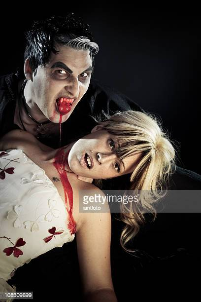 Vampire biting a young woman.