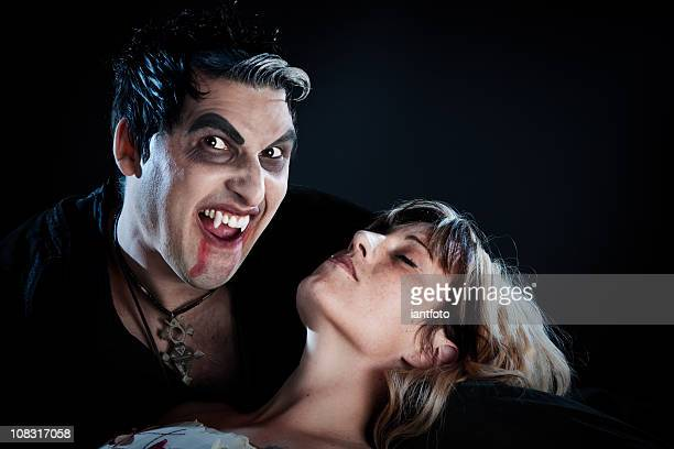 vampire biting a young woman. - zombie girl stock photos and pictures