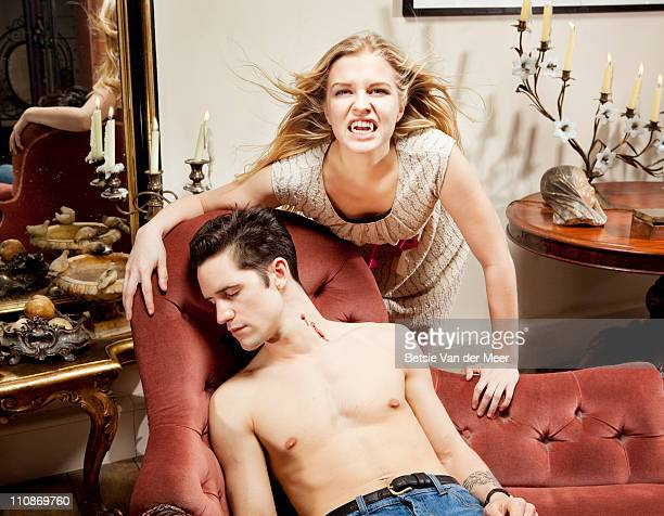 Vampire leaning over dead man on sofa.